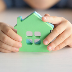 Child holding toy house